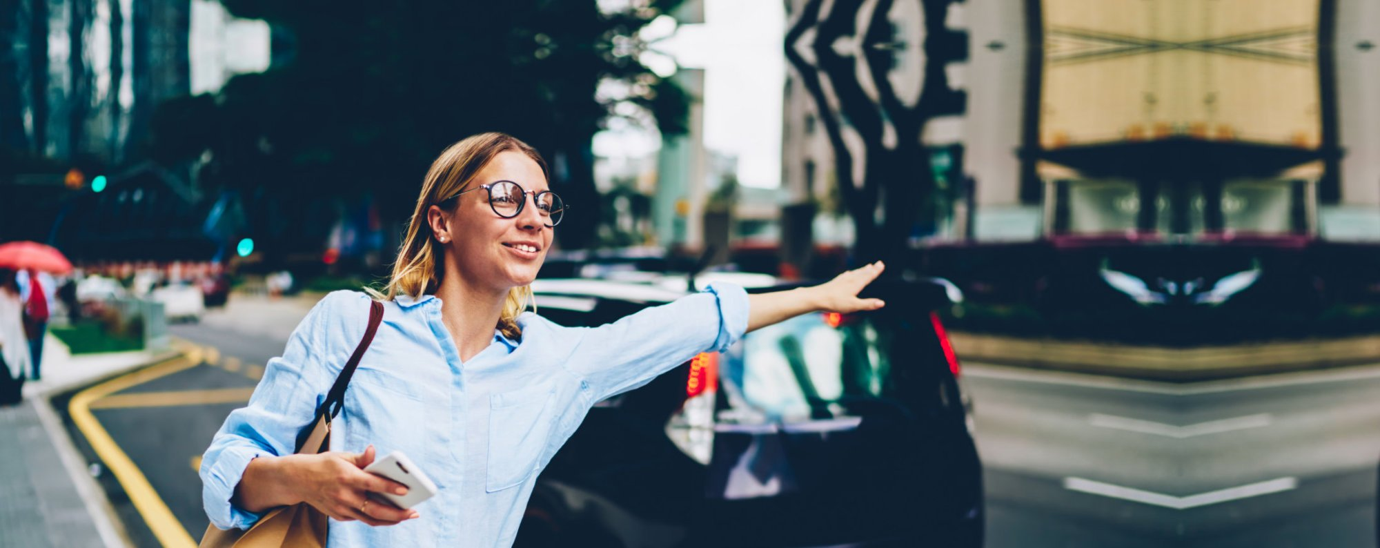 woman waving for taking a car in downtown area